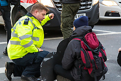 PICTURED: A police officer talks with an anti-pollution protester sitting on the road at Marble Arch. Demonstrators from the anti-pollution group Stop Killing Londoners cause traffic chaos for London commuters as they conduct a series of short roadblocks at Marble Arch stopping cars and buses from entering Oxford Street and Park Lane. Irate motorists accused them of creating more pollution than they were stopping, whilst the group said their objectives were long term. A leaflet handed out to motorists says the government is not doing enough to tackle the crisis costing 'taxpayers and the NHS £billions [sic] a year'. PLACE, January 29 2018. © Paul Davey