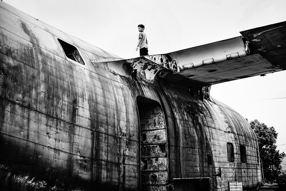 A boy plays on a downed US warplane, which now rests on display in Phuoc Long, Vietnam. 2014