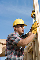 Construction worker using spirit level on building