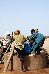 Niger, Agadez, Tidene, 2007. Tuareg nomads struggle to empty a well that became tainted. One man is thirty feet below removing blockage.