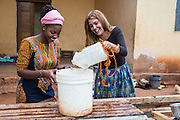 VSO ICS volunteers Francisca Mlingwa and Josie Kearney gather water for cooking in their host home. Volunteers stay with local families get the full experience. Lindi, Lindi region. Tanzania.