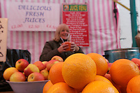 Close-up of oranges on display with senior owner in background