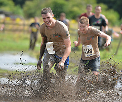 """© Licensed to London News Pictures. 28/07/2013. Competitors take part in the 2013 Tough Guy """"Nettle Warrior"""" in Perton, Wolverhampton. Nettle Warrio is the Summer version of Winter Tough Guy. Run at the end of July it focuses less of the cold and more of the pain for the competitors. Photo credit:  Mike King/LNP"""