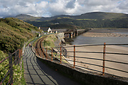 A lady walker on Barmouth's pedestrian and rail bridge on the Mawddach Estuary, on 13th September 2018, in Barmouth, Gwynedd, Wales.