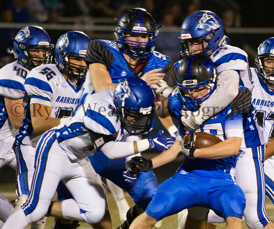 Nick Kruse, right, and Brendan Shackles of Harrisonville wrap up Grain Valley tight end Ryan Brown in the Class 4, District 6 championship Friday night at Grain Valley. The Wildcat defense came through with a critical stop in the last two minutes to seal the 24-21 win.