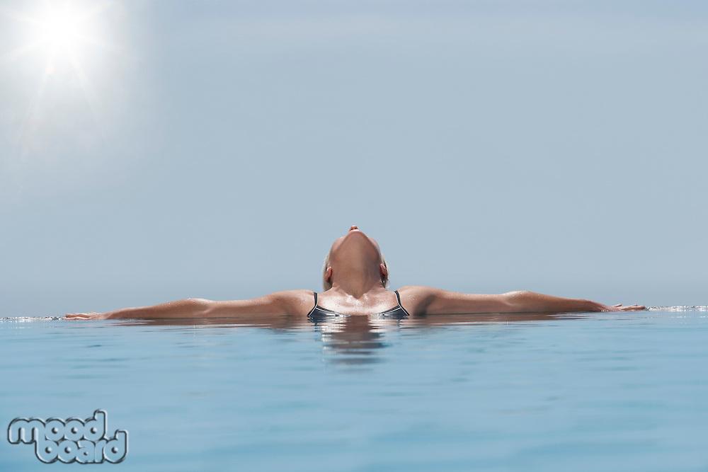 Woman lying head back sunbathing in pool