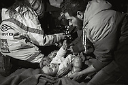 A man tries to calm his injured child, after a crossing of the Aegean Sea. March 20, 2016.