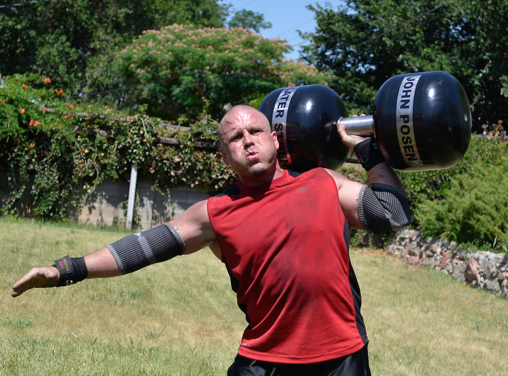 """JD070811e/Sports/07.09.11/Jessica Dyer.Ty Roberts, an Albuquerque medical sales manager and strongman competitor, trains with what's known as a """"circus dumbbell"""" during a July training session at the home of fellow strongman John Posen. Albuquerque, New Mexico(Albuquerque Journal)"""