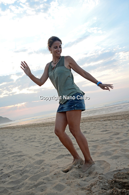 Young attractive woman dancing on the beach