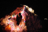 Joe Roberts crawls out of his 10-foot-tall igloo he built in his backyard and decorated with strands of lights.