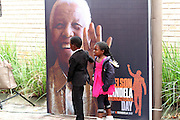 Two kids walking past former president Nelson Mandela larger than life poster at the Nelson Mandela  centre of Memory in Houghton, Johannesburg. Scores of people were brought flowers an lit candles in memory of the fallen hero. Mandela died on the December 5 in his Houghton home.<br /> ©Exclusivepix