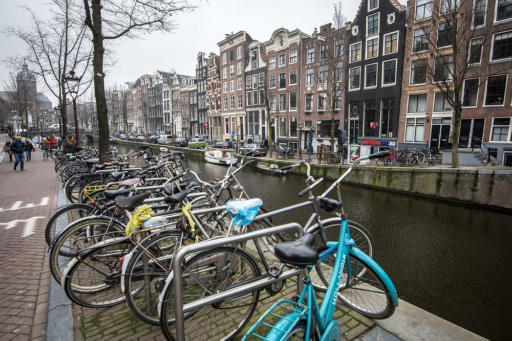 Chained up bikes rest along the side of canal running through the city of  Amsterdam, Netherlands.