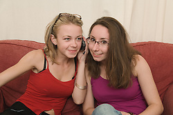 Two Polish students listening to a mobile phone call,