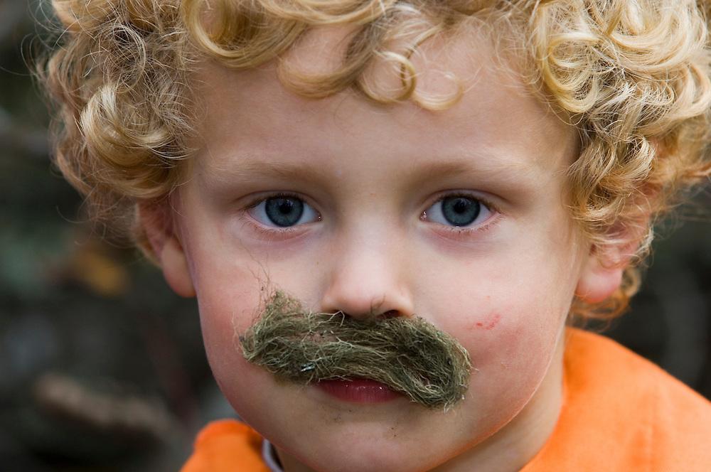 Boy in a Norwegian naturbarnehagen (nature nursery) with a lichen moustache