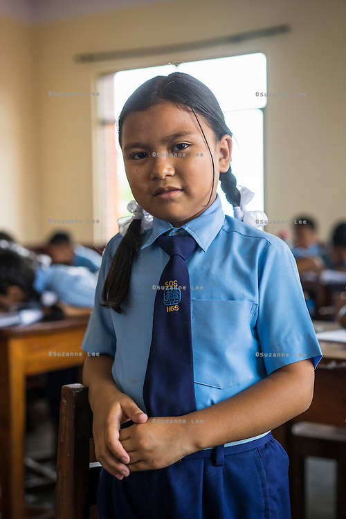Usha (name changed), aged 10, poses for a portrait in her classroom in SOS Children's Villages Sanothimi, Bhaktapur, Nepal on 2 July 2015. Usha's entire family perished when her house collapsed in the earthquake on 25th April 2015. Usha is now well integrated into her new family and school. Photo by Suzanne Lee for SOS Children's Villages