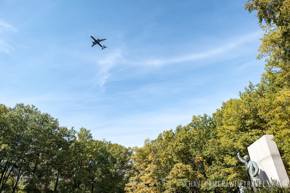 Nestled in the trees, the statue of Theodore Roosevelt stands bottom right at the Theodore Roosevelt Memorial in Arlington, Virginia, just across the Potomac from the National Mall. A plane overhead at top left of frame heads in to land at the nearby Reagan National Airport.