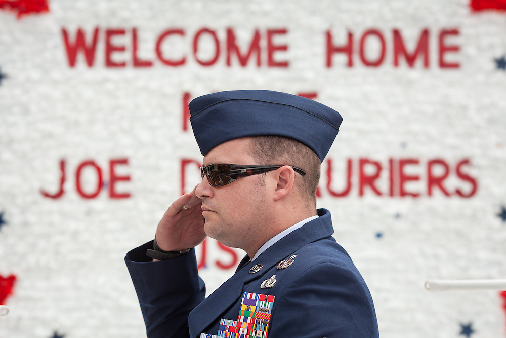 Injured Air Force Master Sgt. Joseph Deslauriers Jr. salutes during the playing of the National Anthem from his position atop a parade float, during a Memorial Day parade where he served as grand marshall in his home town of Bellingham, MA on Sunday, May 19, 2013. The parade was held a week before the holiday to ensure greater attendance. In 2011, Deslauriers lost both of his legs and part of an arm after stepping on an explosive device while stationed in Afghanistan. He is currently rehabbing at Walter Reed Army Medical Center.  (Matthew Cavanaugh for The Washington Post)