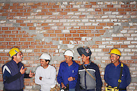 Group of laughing construction workers by brick wall