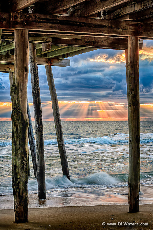 Rays of sun light streak through the clouds at Avalon Fishing Pier in Kill Devil Hills on the Outer Banks.