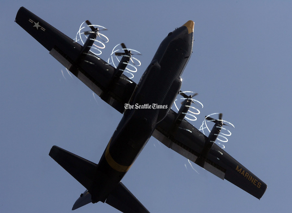 """""""Fat Albert"""", the C-130 supply plane used by the Blue Angels, spins coils of moisture off its propellers during a flyover between hydroplane practice sessions at Lake Washington. (Greg Gilbert / The Seattle Times)"""
