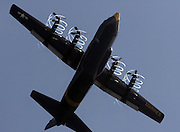 """Fat Albert"", the C-130 supply plane used by the Blue Angels, spins coils of moisture off its propellers during a flyover between hydroplane practice sessions at Lake Washington. (Greg Gilbert / The Seattle Times)"