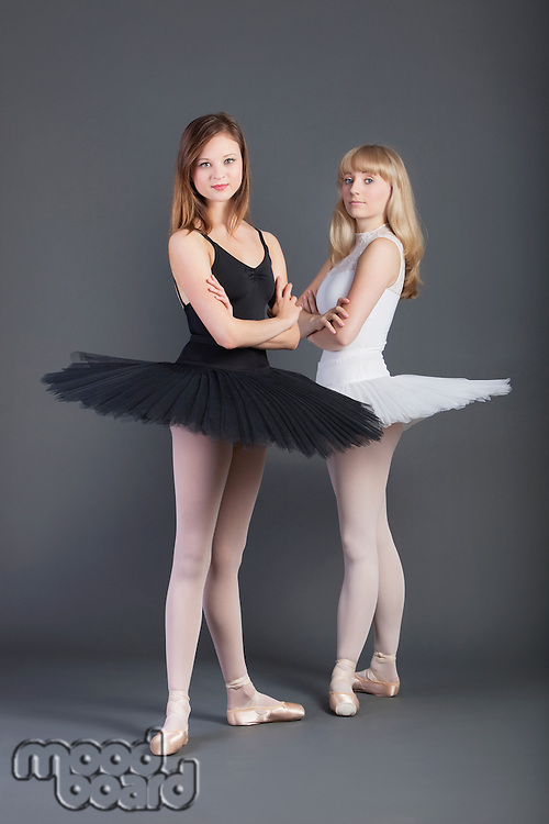 Portrait of two young female ballet dancers with arms crossed standing over grey background