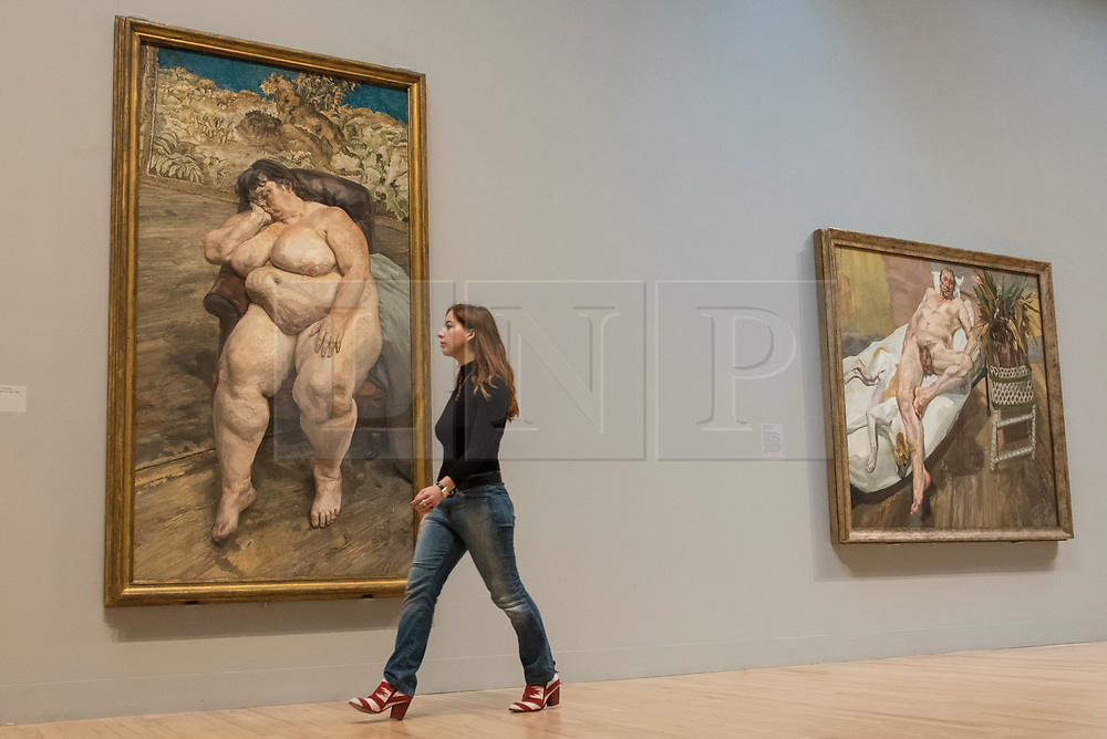 """© Licensed to London News Pictures. 26/02/2018. LONDON, UK. A staff member walks in front of (L to R) """"Sleeping by the Lion Carpet"""", 1996, and """"David and Eli"""", 2003-4, both by Lucian Freud. """"Preview of """"All Too Human"""", an exhibition at Tate Britain which explores how artists in Britain have stretched the possibilities of paint in order to capture life around them.  The exhibition runs 28 February to 27 August 2018 and includes rarely seen works by Lucian Freud and Francis Bacon.  Photo credit: Stephen Chung/LNP"""