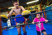 "18 DECEMBER 2104 - BANGKOK, THAILAND: A girl who wants to box works out next to a boxer after a sparring session at the Kanisorn gym. The Kanisorn boxing gym is a small gym along the Wong Wian Yai - Samut Sakhon train tracks. Young people from the nearby communities come to the gym to learn Thai boxing. Muay Thai (Muai Thai) is a Thai fighting sport that uses stand-up striking along with various clinching techniques. It is sometimes known as ""the art of eight limbs"" because it is characterized by the combined use of fists, elbows, knees, shins, being associated with a good physical preparation that makes a full-contact fighter very efficient. Muay Thai became widespread internationally in the twentieth century, when practitioners defeated notable practitioners of other martial arts. A professional league is governed by the World Muay Thai Council. Muay Thai is frequently seen as a way out of poverty for young Thais and Muay Thai camps and schools are frequently crowded. Muay Thai professionals and champions are often celebrities in Thailand.     PHOTO BY JACK KURTZ"