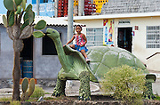 "A girl rides a tortoise sculpture in Puerto Baquerizo Moreno, on Isla San Cristóbal (Chatham Island), which is the easternmost island in the Galápagos archipelago, and one of the oldest geologically. Ecuador, South America. The Galápagos giant tortoise (Chelonoidis nigra, formerly called Geochelone elephantopus) can grow a shell up to about 5 feet (1.5 meters) long (smaller than this supersized sculpture). Published in ""Light Travel: Photography on the Go"" book by Tom Dempsey 2009, 2010."