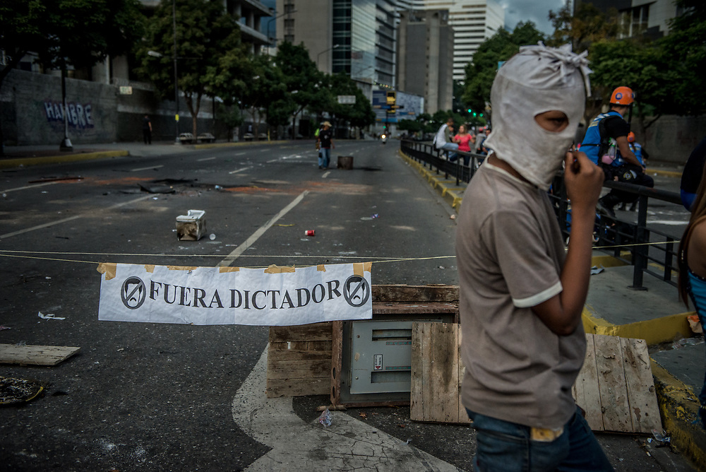 """CARACAS, VENEZUELA - JULY 27, 2017: A road blocked by protesters, with a sign that says """"Go Away Dictator"""" in support of a national strike, called by the political opposition to last for  48 hours, all day July 26th and 27th. They called for their supporters to close businesses, not go to work, and instead create barricades to block off their streets.  Opposition controlled areas of the country were completely shut down.  The strike was called as part of the opposition's civil resistance movement - that began on April 1st, to protest against the Socialist government's attempt to elect a new constituent assembly that will have the power to re-write the constitution, and will threaten democracy.  PHOTO: Meridith Kohut for The New York Times"""