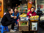 "21 DECEMBER 2017 - HANOI, VIETNAM: A street food vendor in Hanoi's old quarter. The old quarter is the heart of Hanoi, with narrow streets and lots of small shops but it's being ""gentrified"" because of tourism and some of the shops are being turned into hotels and cafes for tourists and wealthy Vietnamese.   PHOTO BY JACK KURTZ"