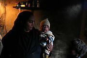 A mother holds one of her children in her home in Khairo Dero village, in Larkana, Pakistan, on Thursday, Jan. 24, 2008. Pakistan is seeking to sustain growth in a country where the government estimates a fourth of the population lives in poverty, or on less than a dollar a day.