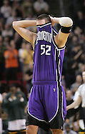 Sacramento Kings' Brad Miller hides his head as he walks down the court during a foul break against the Seattle SuperSonics in Seattle. (AP Photo/John Froschauer)