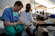 An American doctor  from Christian Church organization pray with his patient praying with her doctor in a volunteer hospital in Port au Prince Haiti after the earthquake...Keeping with a long tradition of Christian missionary work in Haiti, the January 2010 earthquake brought huge numbers of Christian organizations to the country to help the devastated population with food, shelter and spiritual guidance. But the earthquake has had another, less obvious impact. Haiti has a large traditional Voodoo population. Some evangelical Christian groups not only dismiss the Voodoo religion as a Satanic cult, but in fact blame practitioners for the earthquake, saying it was God's punishment. Voodoo spiritual leaders say this belief has led to disparate treatment of earthquake victims by Christian aid groups, with Christian converts getting better tents and food, and Voodoo congregations left unattended. The tension has erupted into violent clashes and attacks on Voodoo temples in Carrefour and Cité Soleil. Voodoo leaders say missionaries are using the promise of food and medical supplies to lure people to religious meetings to convert them and complain international aid is only going to Christian groups.