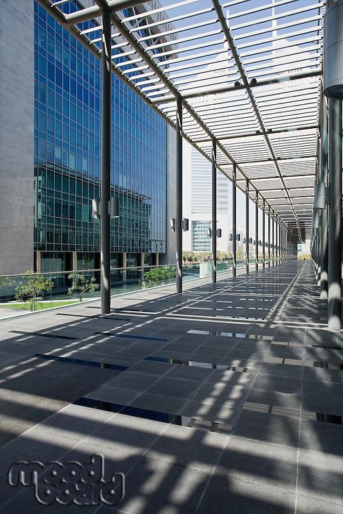 UAE, Dubai, architectural detail of a long outdoor hallway at the Dubai International Financial Centre