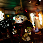 Snowman in a restaurant having a sign Let it snow