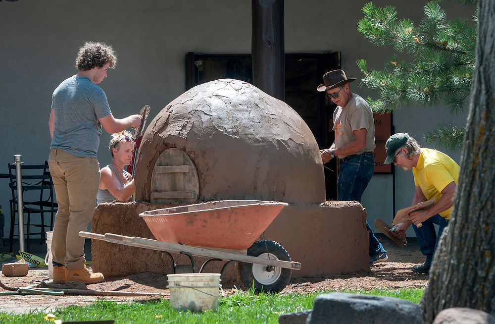 em071917g/jnorth/From left, Adin Lichtenstein, a volunteer from Santa Fe, Leighan Fulfer, from Mountainair and an intern with Corner Stone, Don Dena, from Santa Fe and with Corner Stones and Jeff Davis, from Clovis and a student at at SFCC, finish building a horno in the courtyard of the Palace of the Governor's in Santa Fe, Wednesday July 19, 2017. (Eddie Moore/Albuquerque Journal)