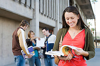 Female university student holding book, outdoors