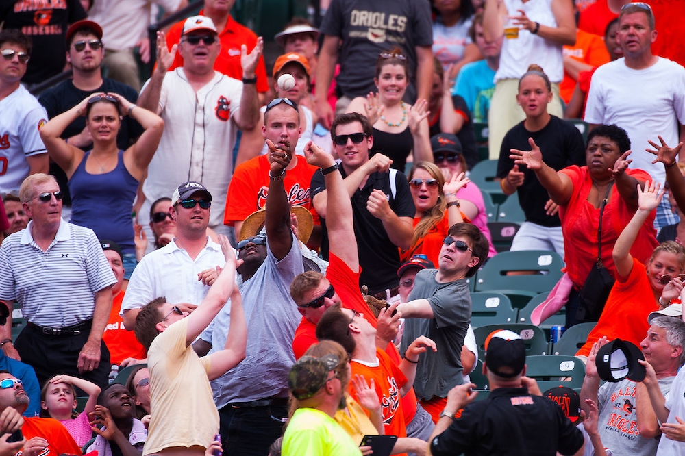 BALTIMORE, MD - MAY 26: Fans reach for a ball in the stands during the game between the Baltimore Orioles and the strikes out at Oriole Park at Camden Yards on May 26, 2012 in Baltimore, Maryland. (Photo by Rob Tringali) *** Local Caption ***