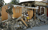 Earthquake aftermath in Haiti on Monday, January 25, 2010..A woman rest on the front porch of a demolished home in Petit Goave caused by the earthquake.