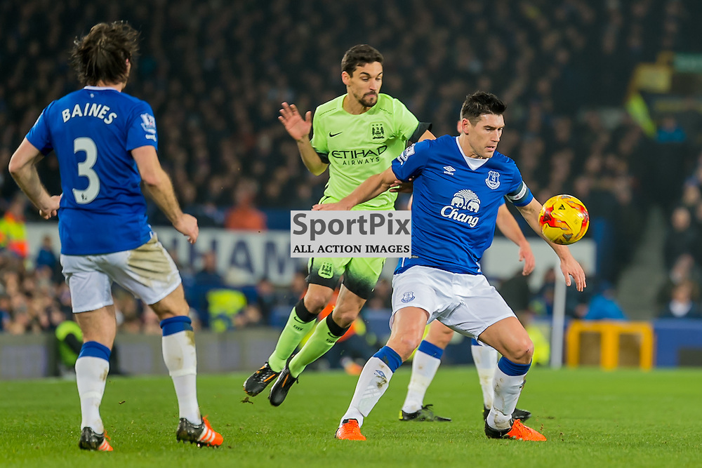 Everton midfielder Gareth Barry shield the ball from Manchester City midfielder Jesus Navas in the Football League cup semi-final first leg at Goodison Park, Liverpool