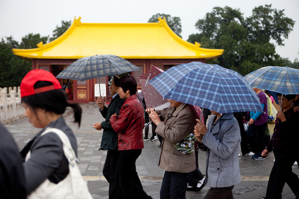 "A group of tourists with umbrellas at ""The Temple of Heaven"" which is a complex of Taoist buildings situated in the southeastern part of central Beijing. Beijing is the capital of the People's Republic of China and one of the most populous cities in the world with a population of 19,612,368 as of 2010."
