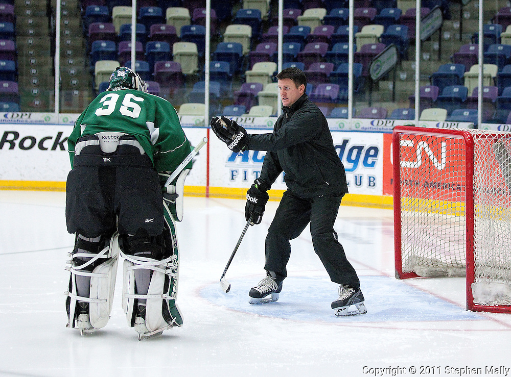 Goaltending coach Scott Meyer (right) talks with RoughRiders goalie Matt McNeely during a practice at the Cedar Rapids Ice Arena, 1100 Rockford Road SW, in Cedar Rapids on Tuesday, December 13, 2011. (Stephen Mally/Freelance)