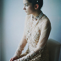 Young adult female sitting quietly alone with sad expression wearing decorative dress with pearl necklace