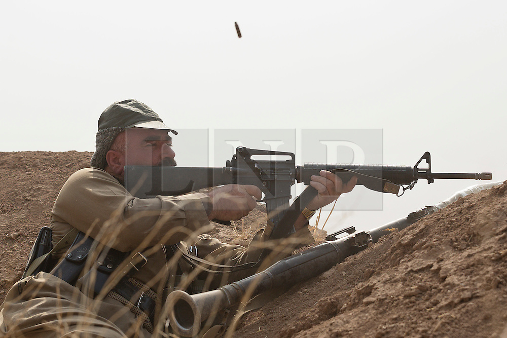 20/10/2016. Bashiqa, Iraq. A Kurdish peshmerga fighter fires his M16 assault rifle at nearby Islamic State positions during an offensive to retake a large area around the ISIS held town of Bashiqa, Iraq, today (20/10/2016).<br /> <br /> Launched in the early hours of today with support from coalition special forces and air strikes, the attack is part of the larger operation to retake Mosul from the Islamic State, and involves both the Kurds and the Iraqi Army. The city of Bashiqa, around 9 miles north of Mosul, is one of several gateway areas that must be taken before any attempted offensive on Mosul itself.<br /> <br /> Despite the peshmerga suffering several casualties after militants fought back using mortars, heavy machine guns and snipers, the Kurdish forces were quickly taking ground with Haider al-Abadi, the Iraqi prime minister, stating that the operation to retake Mosul was progressing faster than expected. Photo credit: Matt Cetti-Roberts/LNP