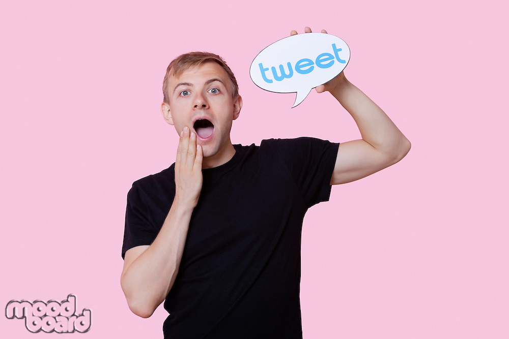 Portrait of surprised young man holding tweet bubble against pink background