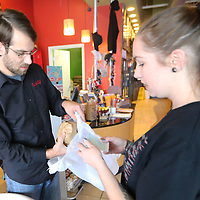 Blake Richardson, a delivery driver for Tupelo 2 Go, receives a customers lunch order from Neon Pig waitress Anna Sparks. Next month, Tupelo 2 Go will celebrate its two-year anniversary. They have expanded their service to include the Mooreville and Saltillo areas and increased their delivery drivers from 4 to 30. Feburary will also be Richardson's two anniversary with the delivery business.