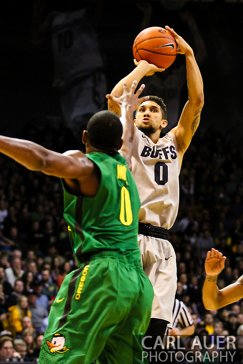 January 5th, 2014:  Colorado Buffaloes junior guard Askia Booker (0) rises up for a shot over Oregon Ducks redshirt senior forward Mike Moser (0) in the second half of the NCAA Basketball game between the Oregon Ducks and the University of Colorado Buffaloes at the Coors Events Center in Boulder, Colorado
