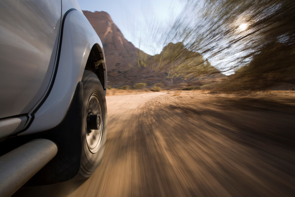 Africa, Namibia, Low-angle view of safari truck driving on dirt road past Spitzkoppe rock formation
