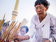 "31 JANUARY 2013 - PHNOM PENH, CAMBODIA:  A Cambodian woman lights incense during a prayer vigil for former King Norodom Sihanouk. Sihanouk (31 October 1922 - 15 October 2012) was the King of Cambodia from 1941 to 1955 and again from 1993 to 2004. He was the effective ruler of Cambodia from 1953 to 1970. After his second abdication in 2004, he was given the honorific of ""The King-Father of Cambodia."" Sihanouk served two terms as king, two as sovereign prince, one as president, two as prime minister, as well as numerous positions as leader of various governments-in-exile. He served as puppet head of state for the Khmer Rouge government in 1975-1976. Most of these positions were only honorific, including the last position as constitutional king of Cambodia. Sihanouk's actual period of effective rule over Cambodia was from 9 November 1953, when Cambodia gained its independence from France, until 18 March 1970, when General Lon Nol and the National Assembly deposed him. Upon his final abdication, the Cambodian throne council appointed Norodom Sihamoni, one of Sihanouk's sons, as the new king. Sihanouk died in Beijing, China, where he was receiving medical care, on Oct. 15, 2012. His funeral procession, which will wind through Phnom Penh is Friday, Feb.1 and his cremation is on Feb. 4, 2013. Over a million people are expected to attend the service.    PHOTO BY JACK KURTZ"